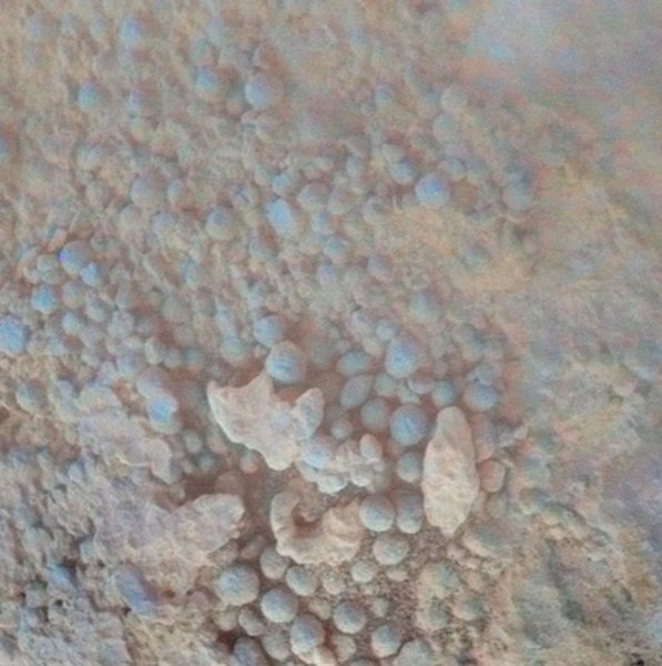 This microscopic image from the NASA's Mars Exploration Rover Opportunity shows details of the coating a rock called Chocolate Hills, which the rover found and examined at the edge of a young crater called Concepcion. The rover used the tools on its robotic arm to examine the texture and composition of target areas on the rock with and without the dark coating. The rock is about the size of a loaf of bread. Initial analysis was inconclusive about whether the coating on the rock is material that melted during the impact event that dug the crater. Images taken through three of the filters are combined into this false-color view of the rock, which is about the size of a football. UPI/NASA