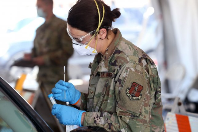 Illinois National Guard member Hannah Gonder inspects a test swab at a COVID-19 testing site in East St. Louis on May 28. President Donald Trump on Monday authorized extensions for National Guard members to continue assisting in states' pandemic response. File Photo by Bill Greenblatt/UPI