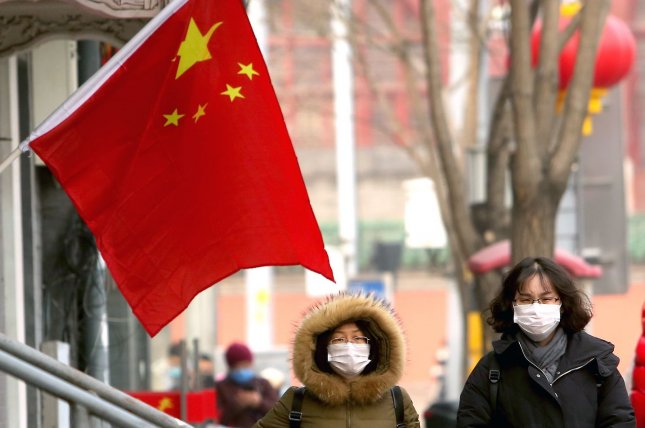 People in Beijing, China, are seen wearing protective face masks on Sunday to guard against a coronavirus outbreak that has so far killed 81 people in mainland China. Photo by Stephen Shaver/UPI