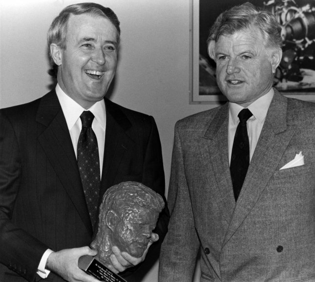 "Canadian Prime Minister Brian Mulroney enjoys a light moment after receiving a gift of the bust of the late John F. Kennedy from Massachusetts Senator Edward M. Kennedy (R) prior to a tour of the John F. Kennedy Library in Boston on May 3, 1989. Mulroney, during his two day stay in Boston, will receive the Christian A. Herter Memorial Award, given to individuals who contributed to ""better international understanding."" (UPI Photo/Stuart Cahill/Files)"