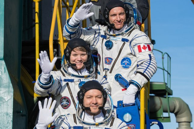 NASA flight engineer Anne McClain (center), shown here before takeoff from Kazakhstan in December, was set to make the first all-female spacewalk this week before it was canceled. File Photo by Aubrey Gemignani, NASA/UPI
