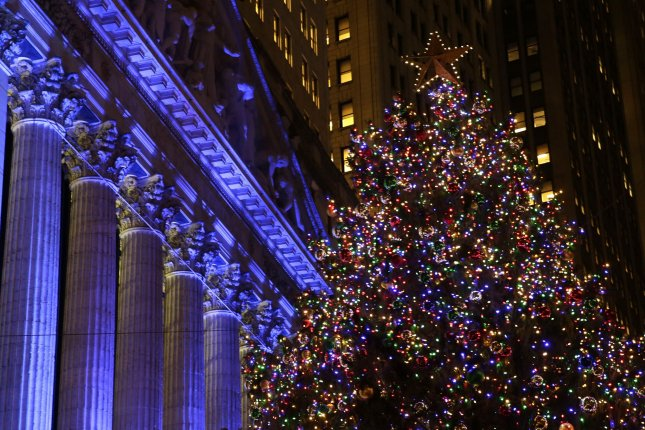 People gather near a Christmas Tree on Wall Street in New York City on Dec. 1. Wednesday, the Dow and S&P 500 closed at new record highs -- placing the Dow within 451 points of the 20,000-mark, which many experts will be achieved before 2016 is out. Photo by John Angelillo/UPI