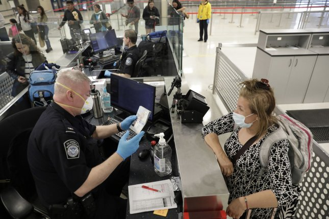 Officers with U.S. Customs and Border Protection Office of Field Operations screen international passengers arriving at Dulles International Airport in Dulles, Va., on Friday. On Thursday, the State Department advised all Americans to stop international travel. Photo by Glenn Fawcett/U.S. Customs and Border Protection