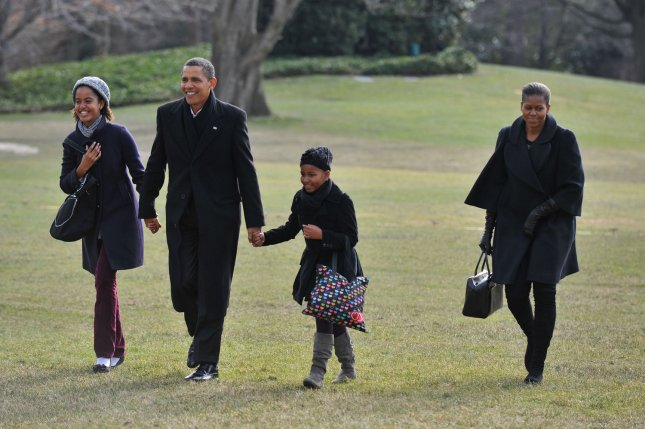 President Barack Obama holds hands with his daughters Sasha (R) and Malia as First Lady Michelle Obama follows as they return to the White House following a family vacation in Hawaii, in Washington on January 4, 2010. UPI/Kevin Dietsch