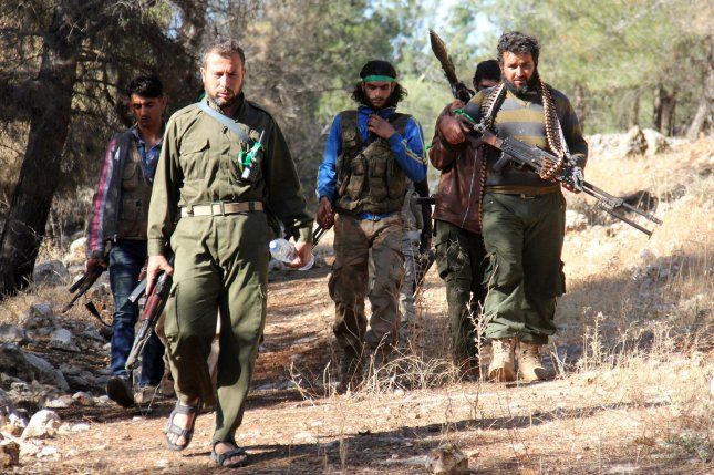 Fighters from a coalition of rebel groups called Jaish al Fateh, also known as Army of Fatah (Conquest Army), move through the countryside of Idlib province, Syria, on June 5, 2015, during fighting with the Syrian military near the town of Psoncol. On Nov. 17, 2015, an alliance of rebel cells in Aleppo and Idlib provinces said they were prepared to fight under the banner of the Syrian Democratic Forces, a coalition of Kurdish, Syriac Christian and Arab rebel groups that has made gains with the help of U.S. airstrikes against Islamic State militants in the al-Hasakah province, to the east. Photo by Omar Haj Kadour/ UPI
