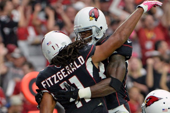 Arizona Cardinals' Larry Fitzgerald (L) is congratulated by Adrian Peterson after scoring on a touchdown in the second quarter against the Tampa Bay Buccaneers at University of Phoenix Stadium in Glendale, Arizona on October 15, 2017. File photo by Art Foxall/UPI