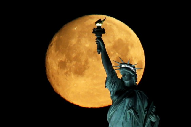 A Super Worm Moon sets behind The Statue Of Liberty shortly before sunrise on Sunday, in New York City. Each month's full moon has been given different nicknames based on the time of year in which it occurs. Photo by John Angelillo/UPI