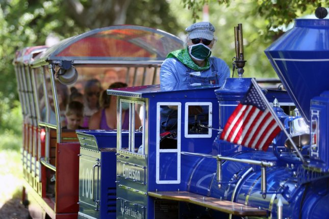 A masked engineer operates a train at the Saint Louis Zoo in St. Louis, Mo., on June 11. The zoo reopened last month after weeks of closure due to the coronavirus pandemic, allowing some employees to return to work. File Photo by Bill Greenblatt/UPI