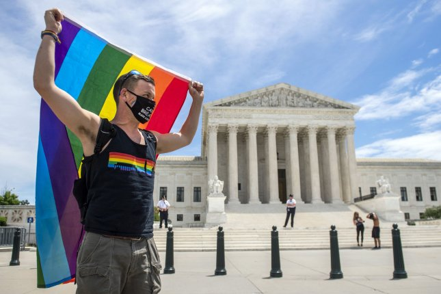 A man carries a rainbow flag in front of the U.S. Supreme Court in Washington, D.C., after a high court ruling banned LGBTQ+ employment discrimination on June 15, 2020. File Photo by Kevin Dietsch/UPI