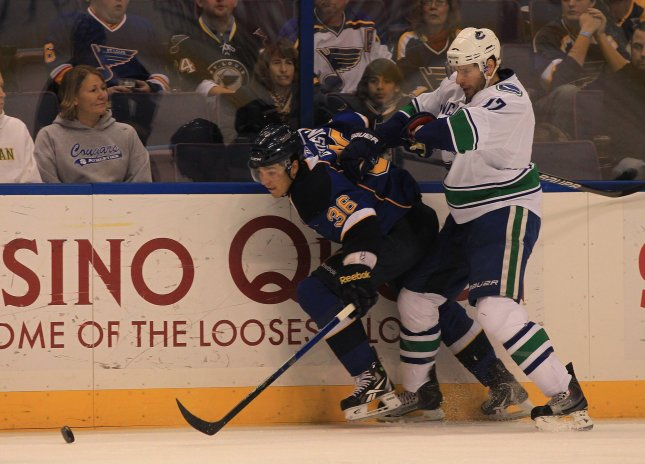 Vancouver Canucks Ryan Kesler (R) tries to push St. Louis Blues Matt D'Agostini pff of the puck in the first period at the Scottrade Center in St. Louis on December 20, 2010. UPI/Bill Greenblatt