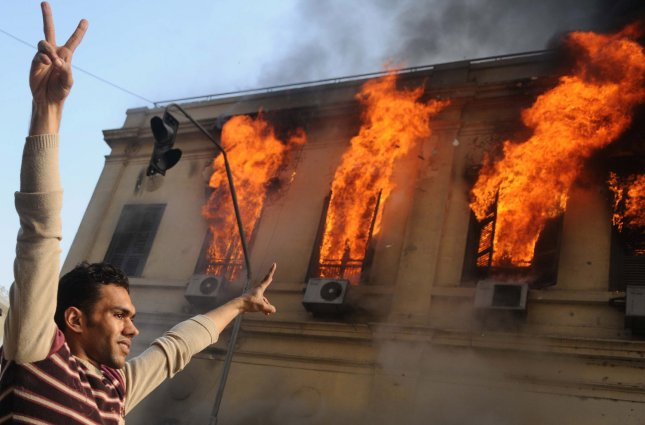 An Egyptian demonstrator makes victory signs near a burning building during clashes with security forces near Cairo's Tahrir Square on December 17, 2011. Nine people are dead as violence raged for the second day marring the first free election in decades. UPI/Mohamad Hosam