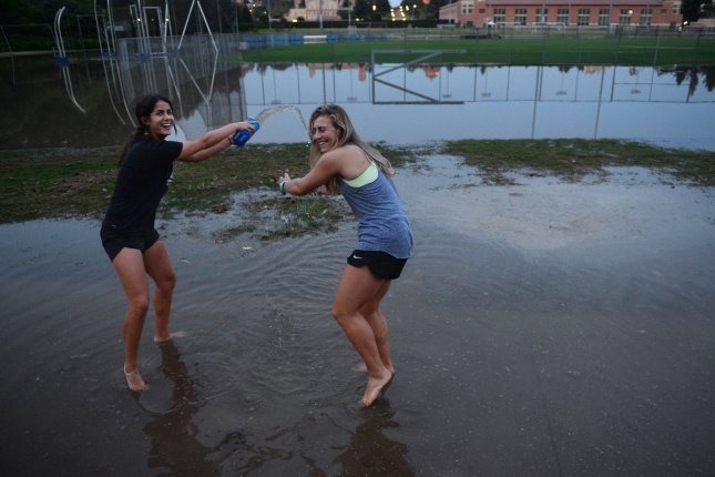 Students Taylor Alberete (L) and Christiana Konkol frolic in a flooded Drake Stadium after a 93-year-old, 30-inch-diameter water main ruptured north of UCLA today, blasting a geyser of water through Sunset Boulevard and sending an estimated 8 million to 10 million gallons cascading down the street and inundating a number of vehicles as it made its way onto the university grounds in Los Angeles on July 29, 2014. UPI/Jim Ruymen