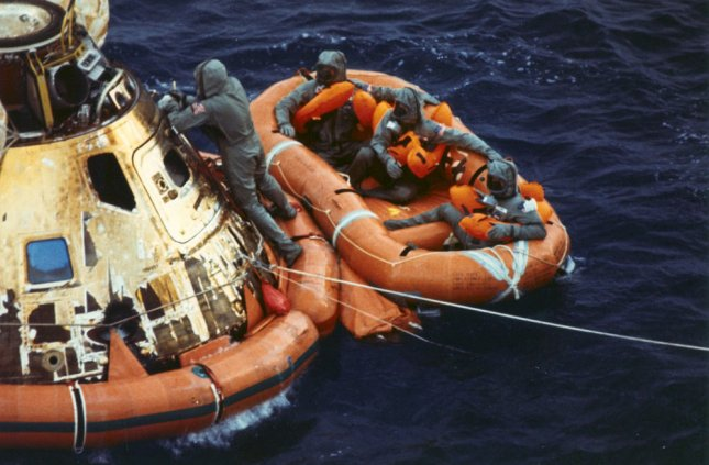 Navy frogman Clancy Hatleberg closes the Apollo 11 spacecraft hatch while astronauts Neil Armstrong, Michael Collins and Buzz Aldrin await a helicopter pickup from their life raft after they splashed down 900 miles southwest of Hawaii July 24, 1969, ending their historic moon mission. (UPI Photo/NASA)