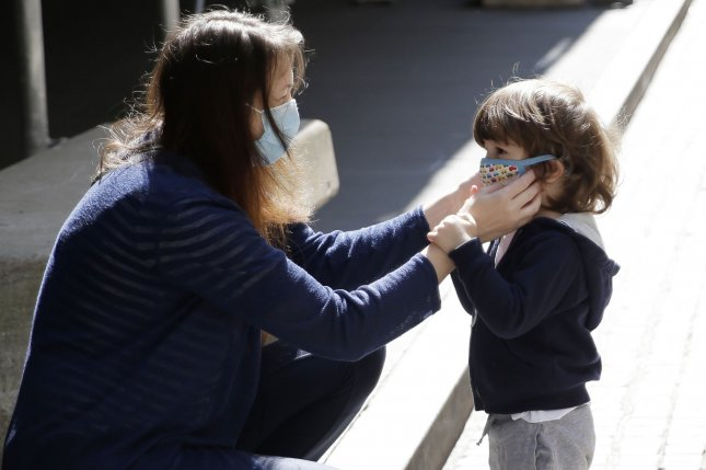 A woman adjusts a face mask on a young child in New York City. The new wave of coronavirus cases nationwide is beginning to seriously strain some critical medical care providers, officials say. File Photo by John Angelillo/UPI