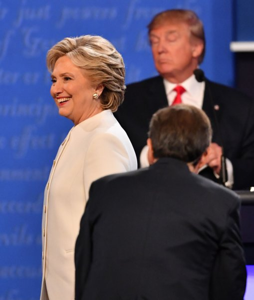 Democratic presidential candidate Hillary Clinton smiles as she walks between moderator Chris Wallace and Republican presidential candidate Donald Trump following their debate at the University of Nevada, Las Vegas on October 19. The UPI/CVoter daily presidential tracking poll released Monday shows Clinton leading Trump by 3.07 percent. Photo by Kevin Dietsch/UPI