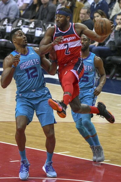 Washington Wizards guard John Wall makes a pass under the basket against Charlotte Hornets center Dwight Howard during their game Saturday. Photo by Mark Goldman/UPI