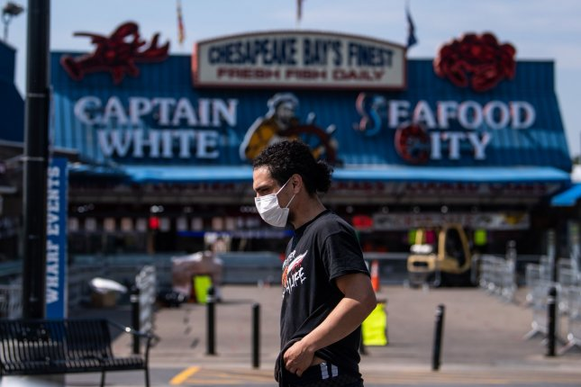 A worker wearing a mask walks through the recently closed D.C. Fish Market at the Wharf in Washington, D.C. on Tuesday. Photo by Kevin Dietsch/UPI