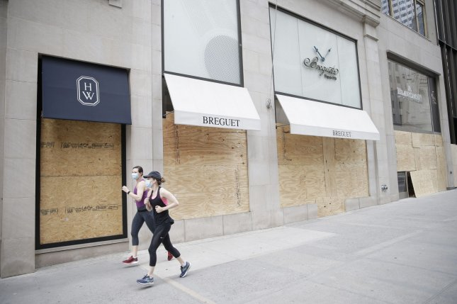 Joggers run past a Breguet retail store that's been boarded up on Fifth Avenue in New York City on Tuesday. The coronavirus outbreak and national unrest over the police killing of George Floyd in Minnesota have significantly impacted retail business in the United States. Photo by John Angelillo/UPI
