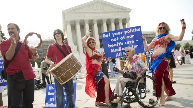 Supporters of a single payer health care system dance in front of the United State Supreme Court on June 28, 2012 in Washington, D.C. The court upheld President Obama's health care reform bill, the Affordable Care Act, Thursday. UPI/Kevin Dietsch