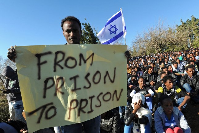 An African asylum seeker holds a poster and an Israeli flag at a protest against Israel's refusal to grant them refugee status outside the Knesset, Israel's Parliament, in Jerusalem last year. Tens of thousands of African immigrants called on Israel to recognize them as refugees and stop a law that allows the authorities to keep them in an open ended detention center in southern Israel. File Photo by Debbie Hill/UPI