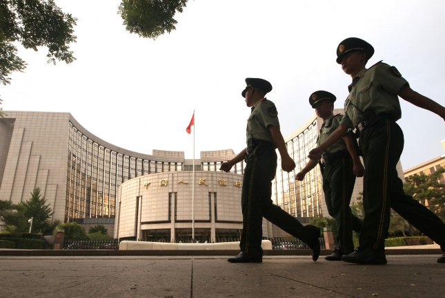 Chinese soldiers march past the People's Bank of China, the country's central bank responsible for carrying out monetary policy and regulation of financial institutions, in Beijing on Tuesday. The Dow fell more than 700 points at one point Monday in trading that was seriously influenced by the ongoing trade conflict with China. Photo by Stephen Shaver/UPI