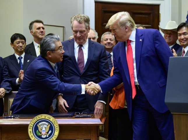 United States President Donald Trump shakes hands with Ambassador Shinsuke Sugiyama of Japan after signing the U.S.-Japan Trade Agreement and U.S.-Japan Digital Trade Agreement. Photo by Ron Sachs/UPI
