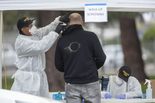 An individual has his temperature checked by a Hayward emergency-medical technician for symptoms and high temperature at a triage station for coronavirus in Hayward, Calif., in March. Photo by Peter DaSilva/UPI