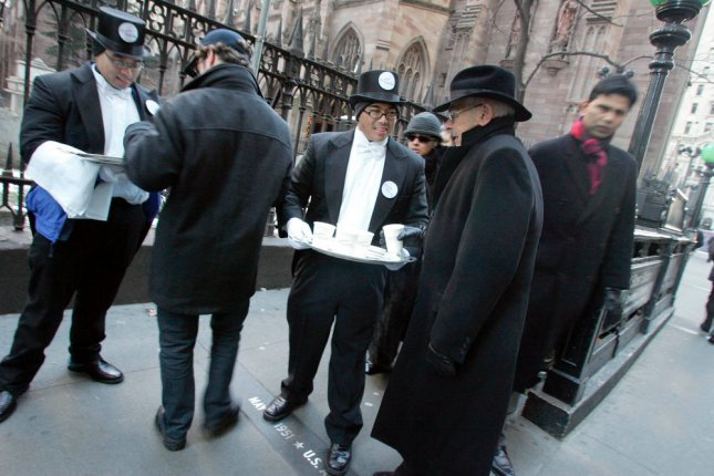 Two cups of cocoa a day may help older people keep brains sharp. Steve Estrellado, third from right, acting as a butler, offers hot chocolate to New Yorkers.. (UPI Photo/Diane Bondareff)