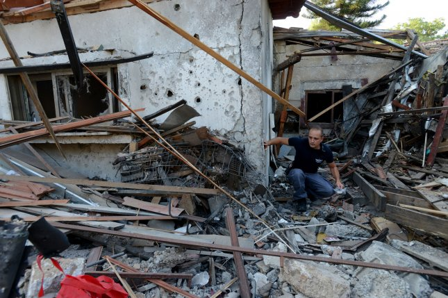 A member of the Israel bomb squad works at a house destroyed by a rocket fired by Palestinian militants in Gaza, in Yehud, near Ben Gurion Airport, Israel, July 22, 2014. The Federal Aviation Administration told U.S. airlines they are prohibited from flying to Tel Aviv's Ben Gurion Airport for 24 hours after the Hamas rocket hit the house in Yehud. Several European airlines have also suspended flights. UPI/Debbie Hill