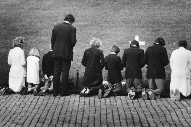 Ethel Kennedy (C), kneeling, is accompanied by her brother-in-law Sen. Edward Kennedy (standing) and some of her children as they pay respects to her husband Robert F. Kennedy at his gravesite at Arlington National Cemetery in Arlington, Va., on June 6, 1979. File Photo by Larry Rubenstein/UPI