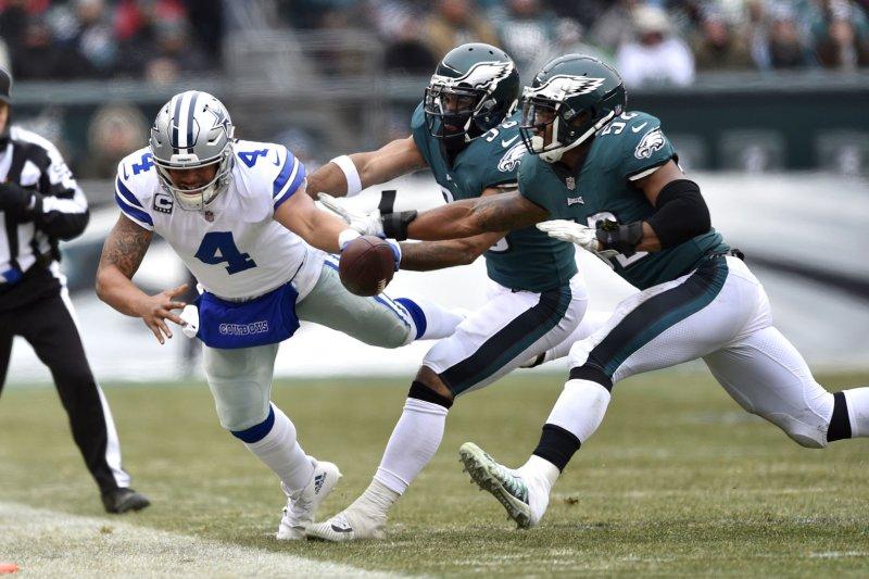 Dallas Cowboys quarterback Dak Prescott (4) dives for extra yards past Philadelphia Eagles defensive end Brandon Graham (55) and linebacker Najee Goode (52) during the second quarter on December 31, 2017 at Lincoln Financial Field in Philadelphia. Photo by Derik Hamilton/UPI