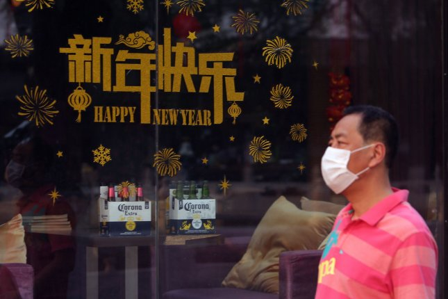 A Chinese man walks past a closed bar while continuing to wear a protective face mask as lockdown restrictions eased across the country. Photo by Stephen Shaver/UPI
