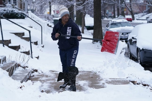 Homeowner Jackie Reid clears the walk in front of her house after nearly 3 inches of snow blanketed St. Louis on January 27. The early morning snow storm was the first measurable snow fall in St. Louis this season. More snow is forecast through the Midwest. File Photo by Bill Greenblatt/UPI