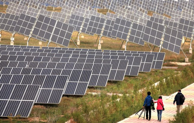 Journalists walk past a massive solar panel field operating in the Taiyangshan Development Zone in Wuzhong, a frontier city in the northwestern province Ningxia Hui Autonomous Region on September 22, 2011. The 215 square mile zone has the advantages of both strong wind and solar power, resulting in 300 megawatts of wind power and 100 megawatts of photovoltaic power. Taiyangshan is the biggest clean energy base in China. UPI/Stephen Shaver