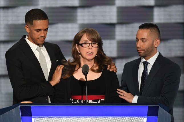 Christine Leinonen, mother of Orlando shooting victim Christopher Drew Leinonen, is joined onstage by her late son's friends, Brandon Wolf, left, and Jose Arraigada, as she addresses delegates during day three of the Democratic National Convention at the Wells Fargo Center in Philadelphia on Wednesday. Leinonen was one of several relatives of victims killed in mass shootings who urged delegates Wednesday to fight for tougher gun control laws. Photo by Pat Benic/UPI
