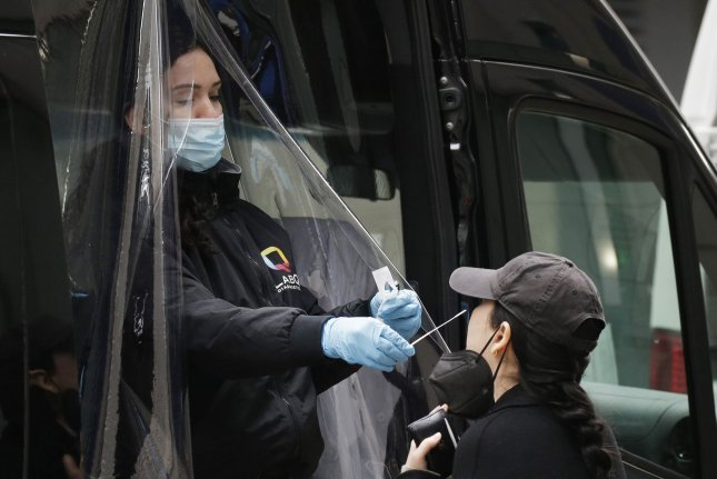 A woman receives a coronavirus test from a van near Rockefeller Center in New York City on April 2. File Photo by John Angelillo/UPI