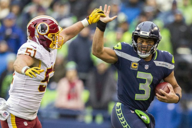 Seattle Seahawks quarterback Russell Wilson (3) fends off the attempted tackle by Washington Redskins inside linebacker Will Compton (51) as he runs for a 13-yard gain during the third quarter in their game at CenturyLink Field in Seattle, Washington on November 5, 2017. File photo by Jim Bryant/UPI
