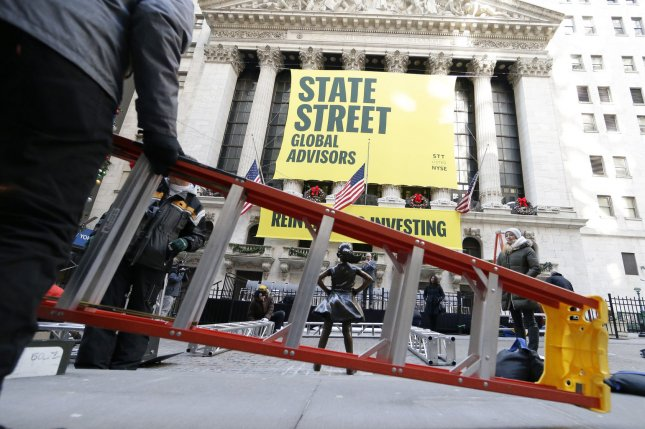 Construction workers pass the Fearless Girl statue outside the New York Stock Exchange on Wall Street in New York City. File Photo by John Angelillo/UPI