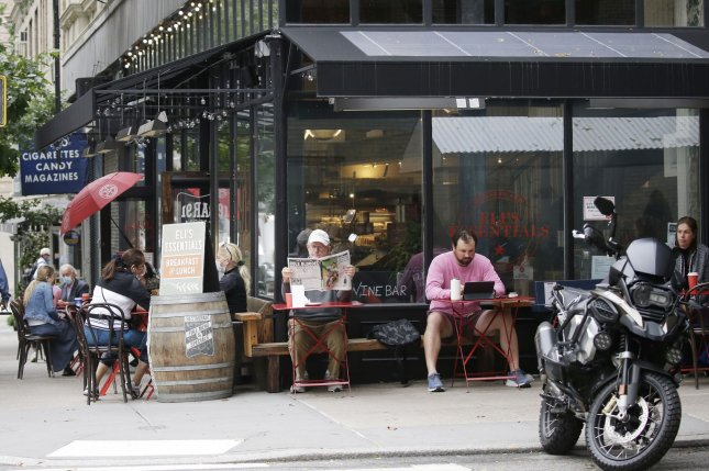 Masked patrons eat outside a restaurant on Madison Avenue in New York City on Wednesday, as restaurants were allowed to resume indoor dining at 25% capacity. Photo by John Angelillo/UPI