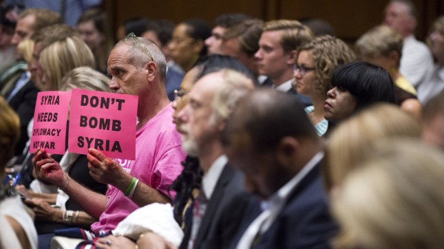 A protester sits in a Senate Foreign Relations Committee hearing on military intervention in Syria with Secretary of State John Kerry and Defense Secretary Chuck Hagel, on Capitol Hill in Washington, D.C. on September 3, 2013. UPI/Kevin Dietsch