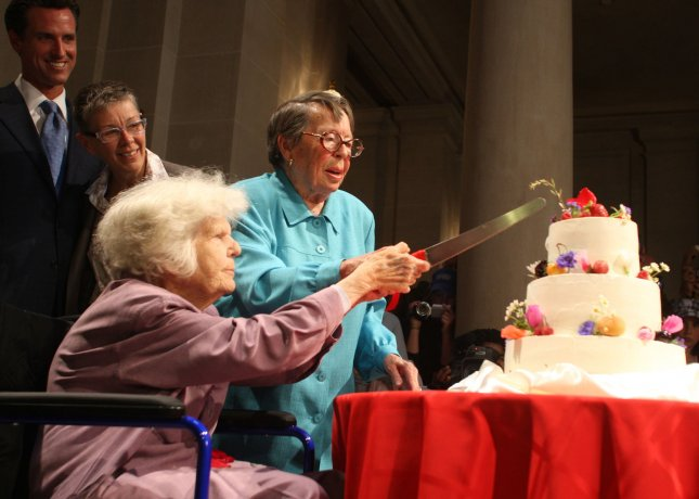 File photo of gay activists Phyllis Lyon (R) and Del Martin cut a wedding cake after being married by Mayor Gavin Newsom (L) in the mayors office in San Francisco on June 16, 2008. (UPI Photo/Terry Schmitt)