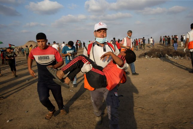 A Palestinian paramedic carries away an injured protester during clashes with Israeli forces across the barbed-wire fence following a demonstration along the border with Israel east of Khan Yunis in southern Gaza on Friday. Photo by Ismael Mohamad/UPI