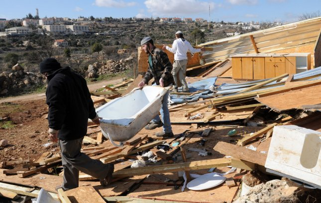 Israeli settlers inspect their destroyed wooden houses in the unauthorized outpost of Mitzpe Avichai near the Kiryat Arba Settlement in Hebron, West Bank, after the outpost was destroyed by the Israeli army, January 12, 2012. Israeli troops destroyed ten houses in the illegal settlement outpost Mitzpe Avichai. UPI/Debbie Hill