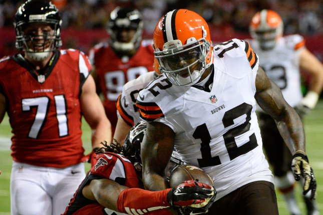 Cleveland Browns wide receiver Josh Gordon (12) drives for extra yardage against Atlanta Falcons safety Dwight Lowery (20) during the first half of their 2014 NFL game at the Georgia Dome in Atlanta. File photo by David Tulis/UPI