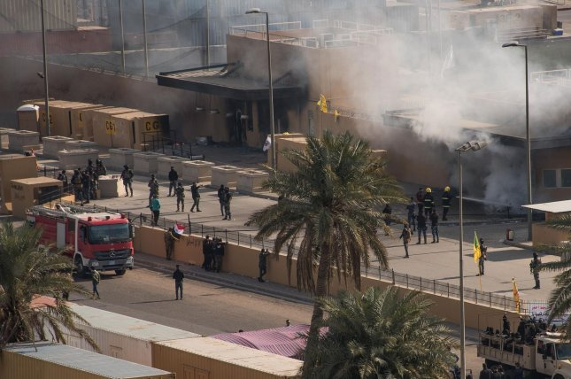Iraqi firemen extinguish a blaze at the gates of the U.S. Embassy compound in Baghdad on Wednesday. Multiple sources reported missiles landed in Baghdad near the U.S. Embassy and near a U.S. air base Saturday. Photo by British Lt. Col. Adrian Weale/Department of Defense
