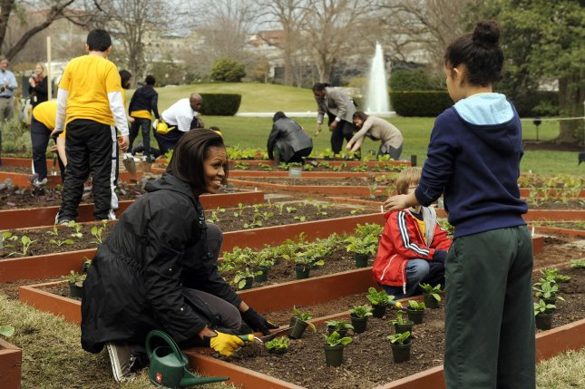 First Lady Michelle Obama and local students plant in the White House Kitchen Garden on the South Lawn of the White House in Washington on March 16, 2011. UPI/Roger L. Wollenberg