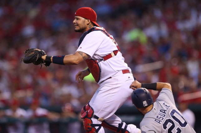 St. Louis Cardinals catcher Yadier Molina waits for the throw that never comes as the San Diego Padres' Carlos Asuaje slides safely into home plate during their game Thursday. Photo by Bill Greenblatt/UPI