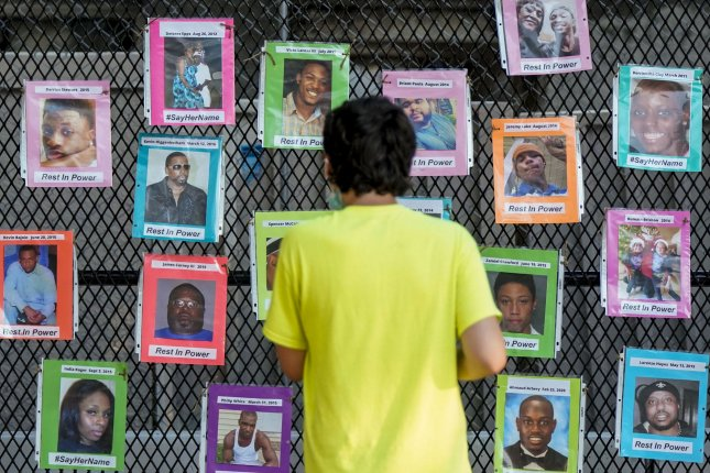 A young man looks at photos of black women and men, whose lives have been lost due to violence, on a fence outside the White House on July 4. Photo by Leigh Vogel/UPI