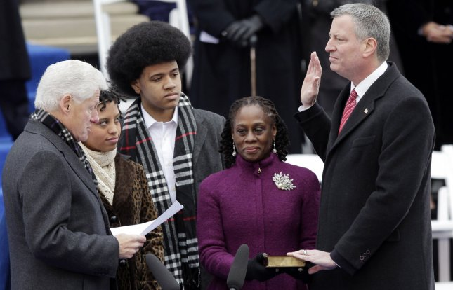 New York City's 109th Mayor Bill de Blasio is sworn in by former President Bill Clinton as his family Chiara de Blasio, Dante de Blasio and wife Chirlane McCray stand with him at the inauguration ceremonies for Mayor-elect Bill de Blasio at City Hall in New York City on January 1, 2014. Mayor de Blasio was sworn in using a Bible once owned by President Franklin Delano Roosevelt f ollowing 12 years of the Michael Bloomberg administration. UPI/John Angelillo