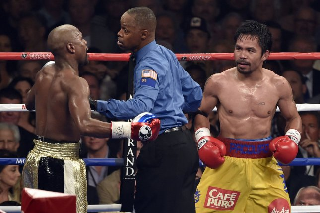 Referee Kenny Bayless separates Floyd Mayweather Jr., left, and Manny Paciquiao during their welterweight unification bout at MGM Grand Garden Arena on May 2 in Las Vegas. Mayweather won with an unanimous decision after the 12 round fight. File Photo by David Becker/UPI